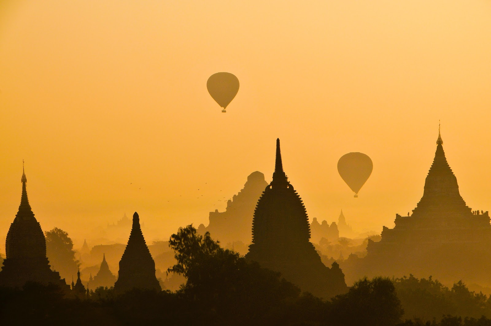 hot air balloons lifting into the sky against a backdrop of pagodas
