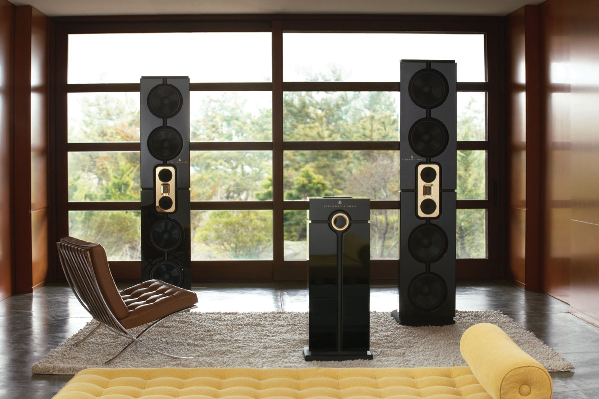 Three SMC Model D black coloured speakers in a living room