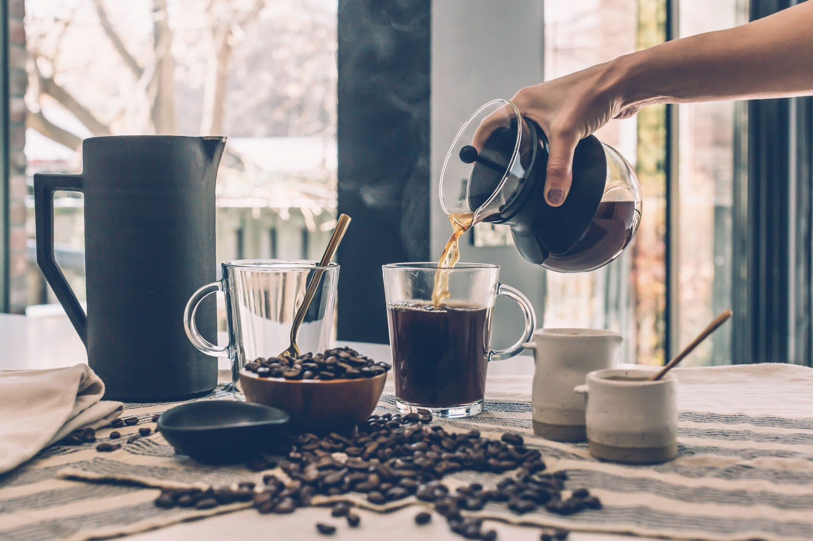 Pouring black coffee into a cup