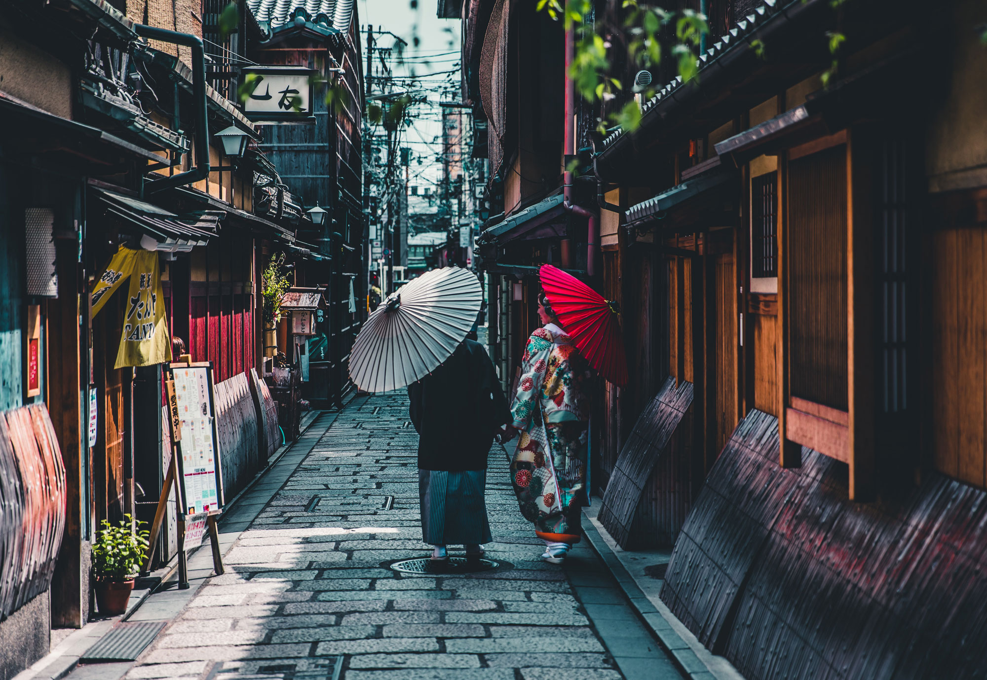 two people in Kimonos walking along the shop houses of Japan
