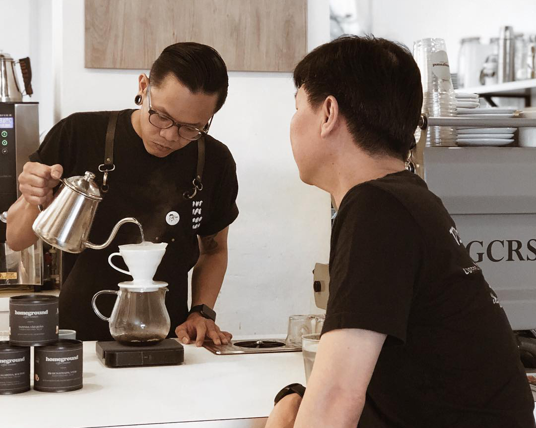 a barista pouring hot water over a filter cup coffee