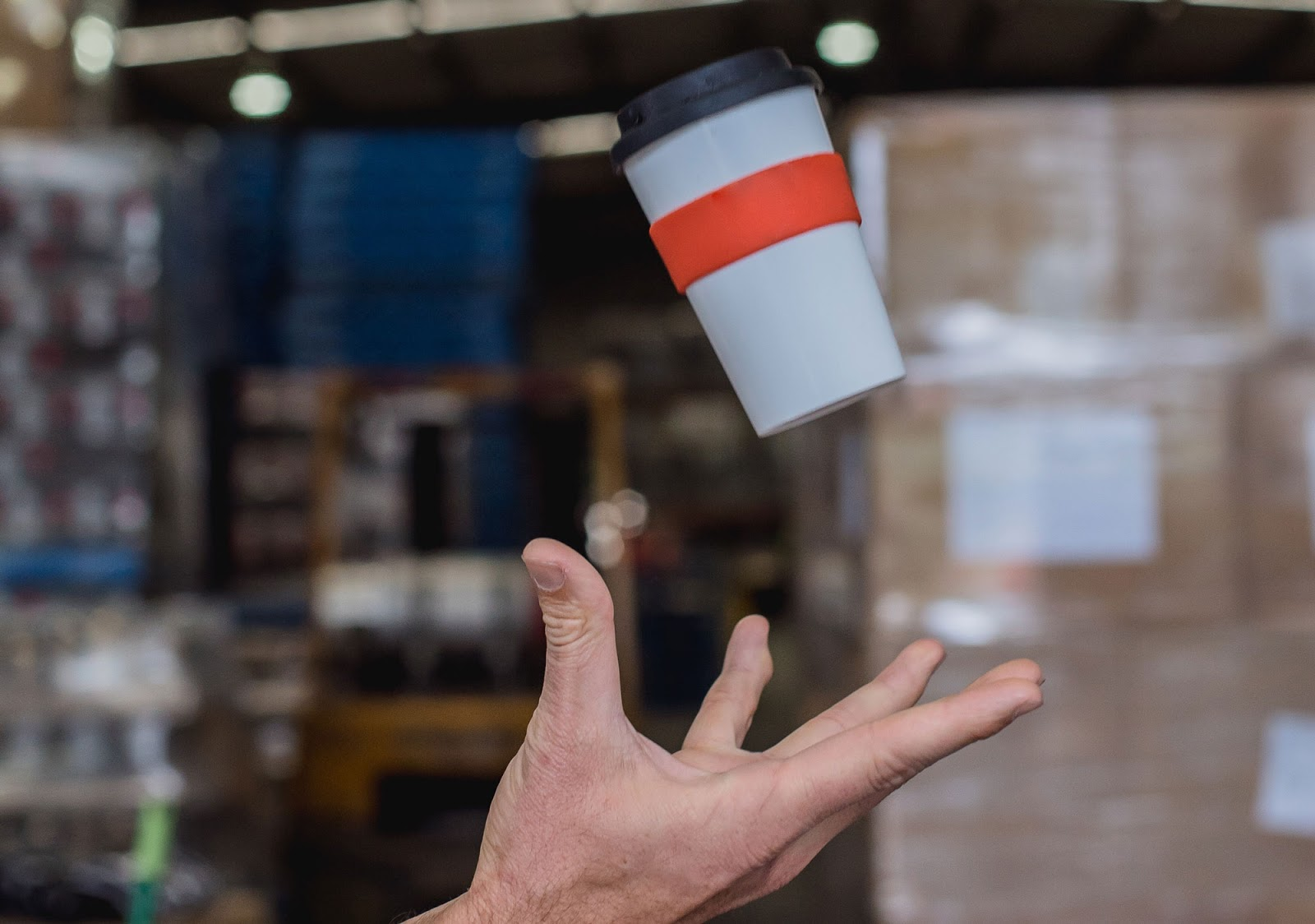 a person throwing a coffee cup into the air