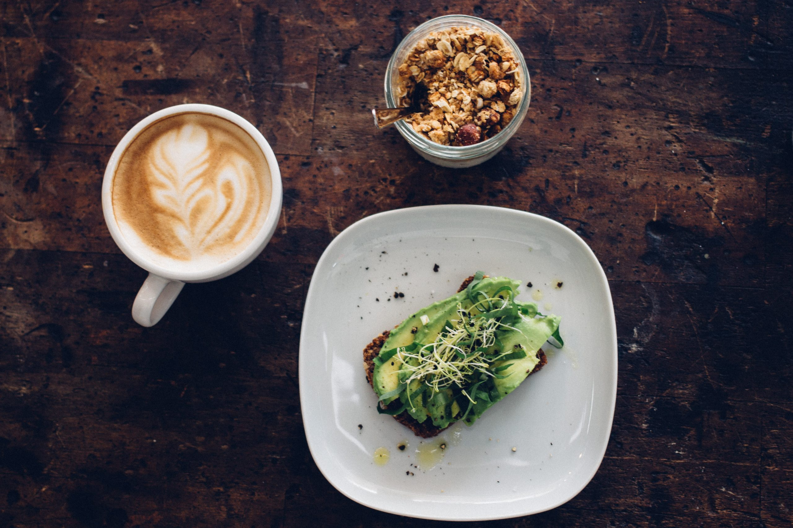 A cup of coffee, granola, and an avocado toast placed on a wooden table