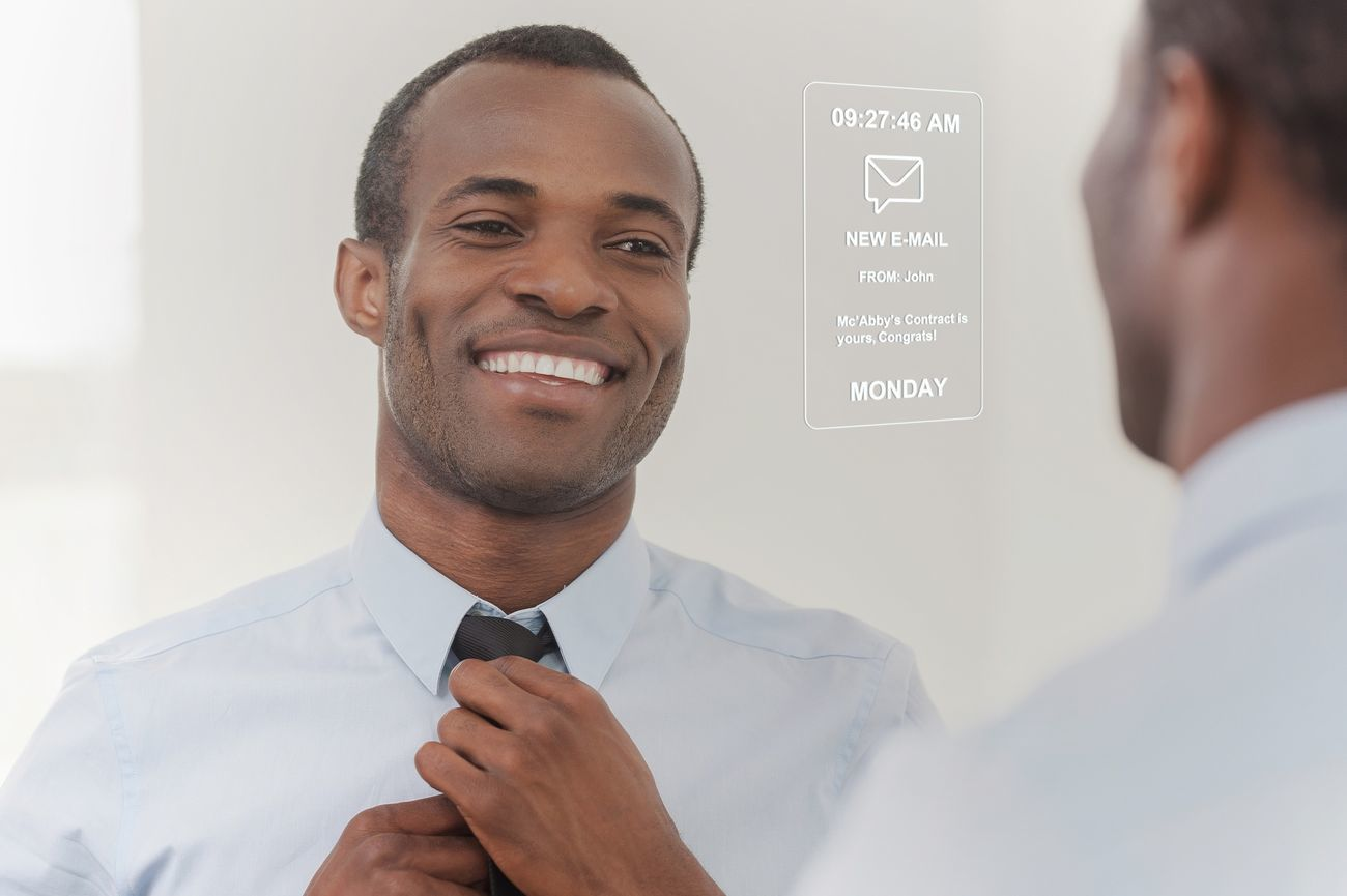 A man adjusting his tie while looking at the mirror