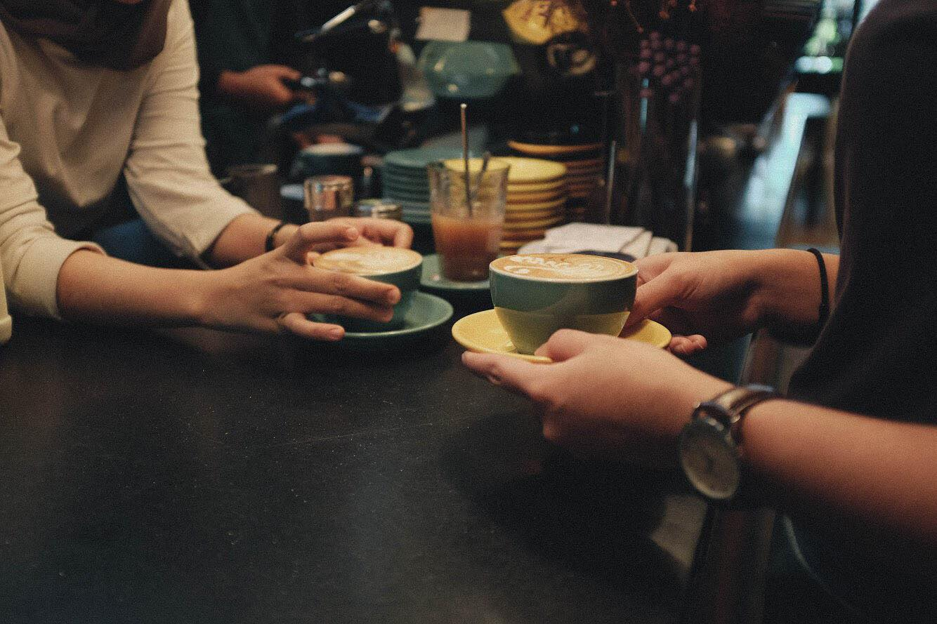 two people having a conversation while having coffee at a cafe