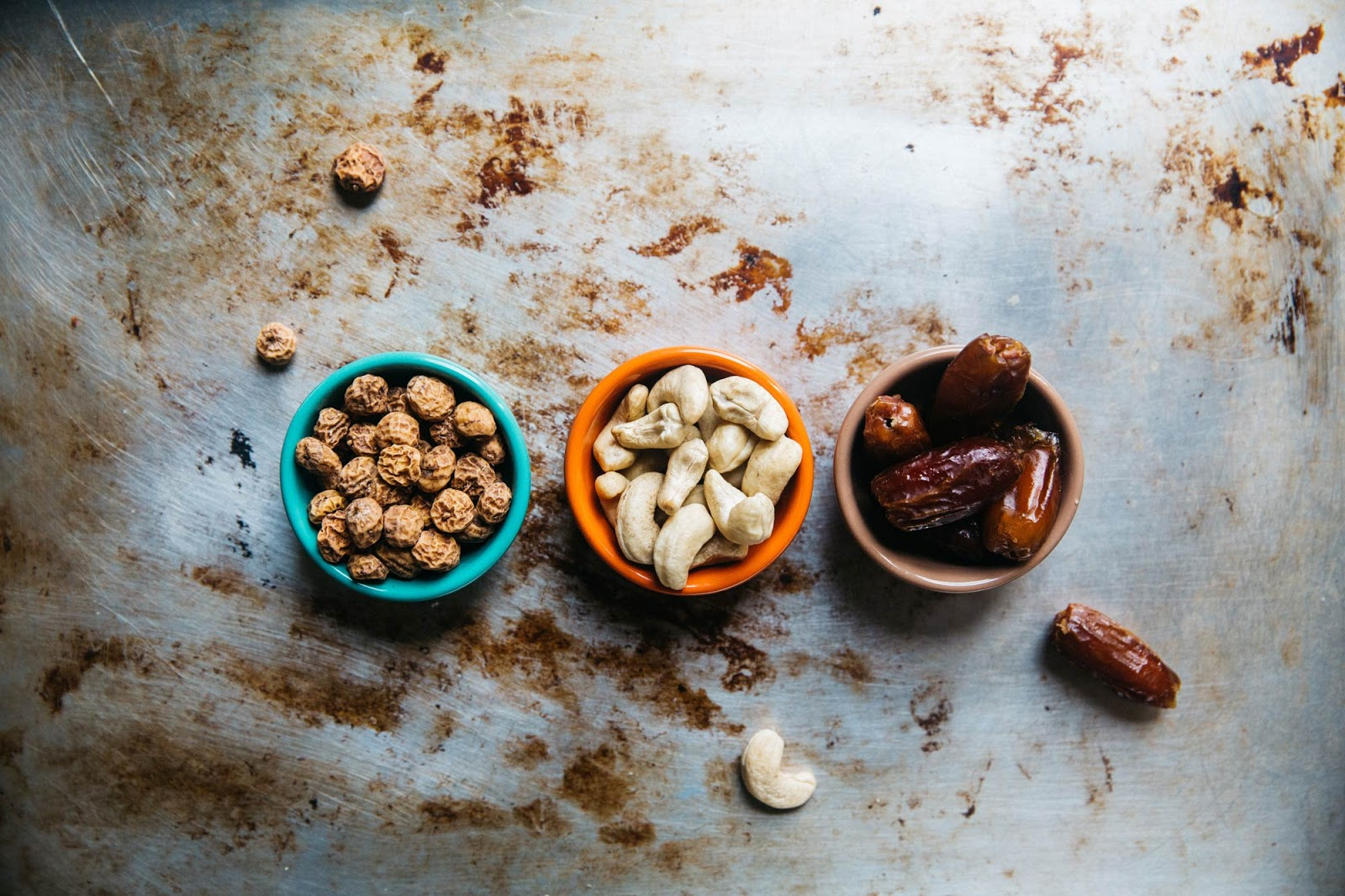 three bowls, each filled with walnuts, cashew nuts, and dates