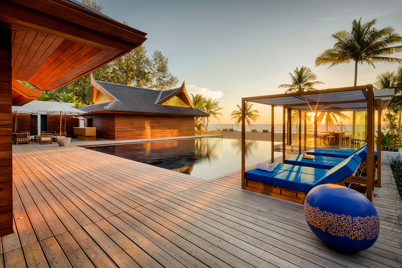 a swimming pool and day beds at a resort in Phuket