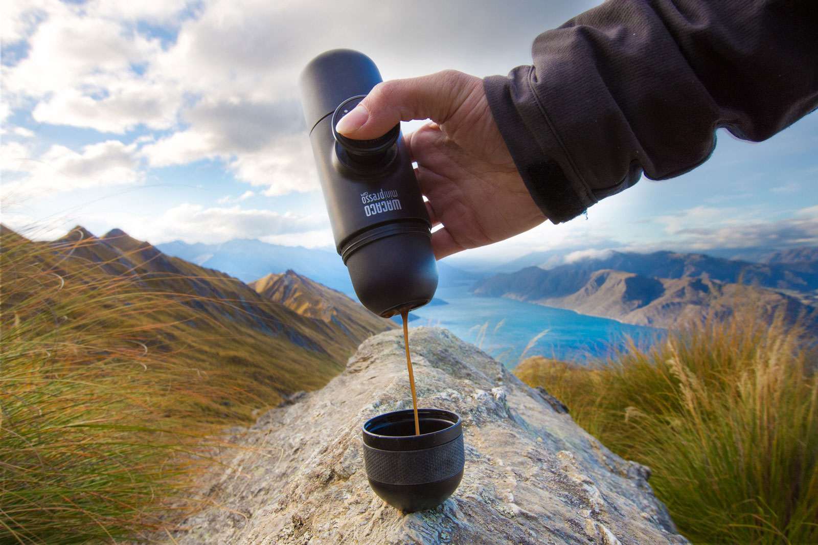 A person making coffee on a mountain using a portable coffee gadget