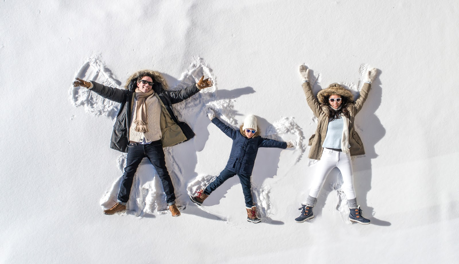 A family of three making snow angels