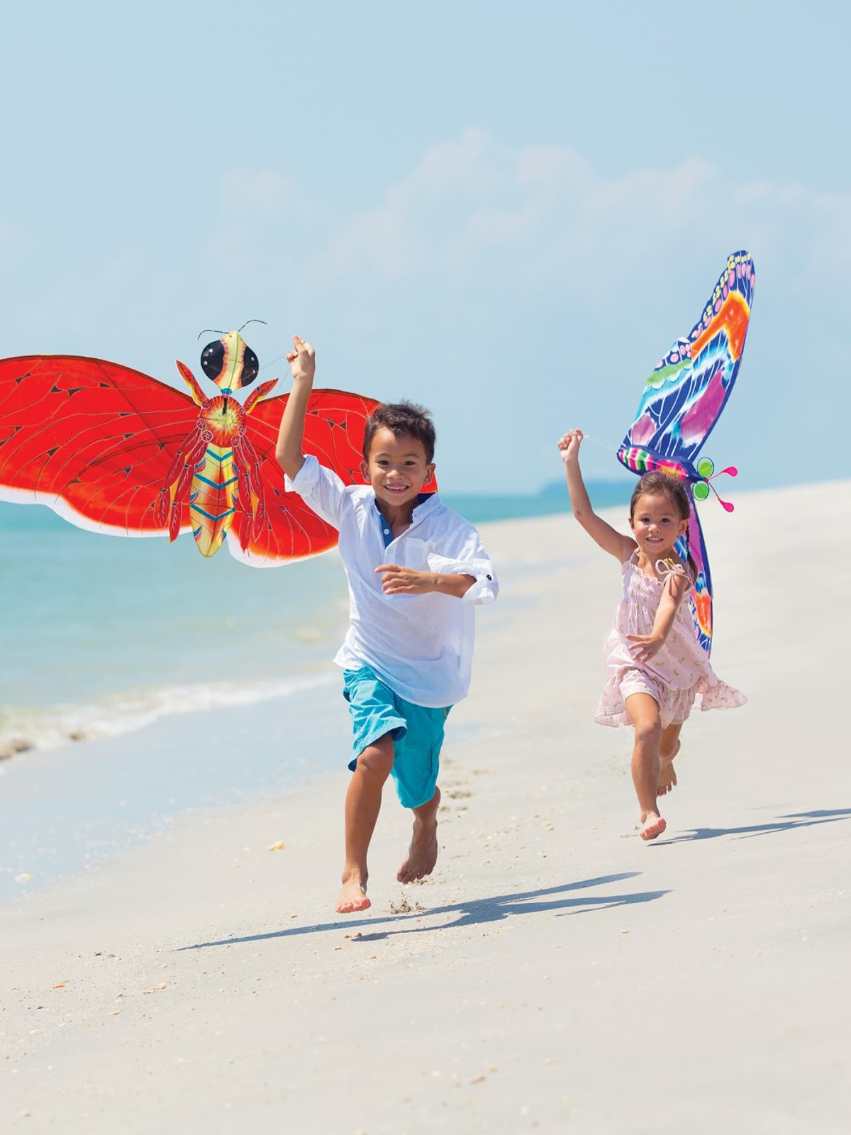 A girl and a boy playing with kites on the beach