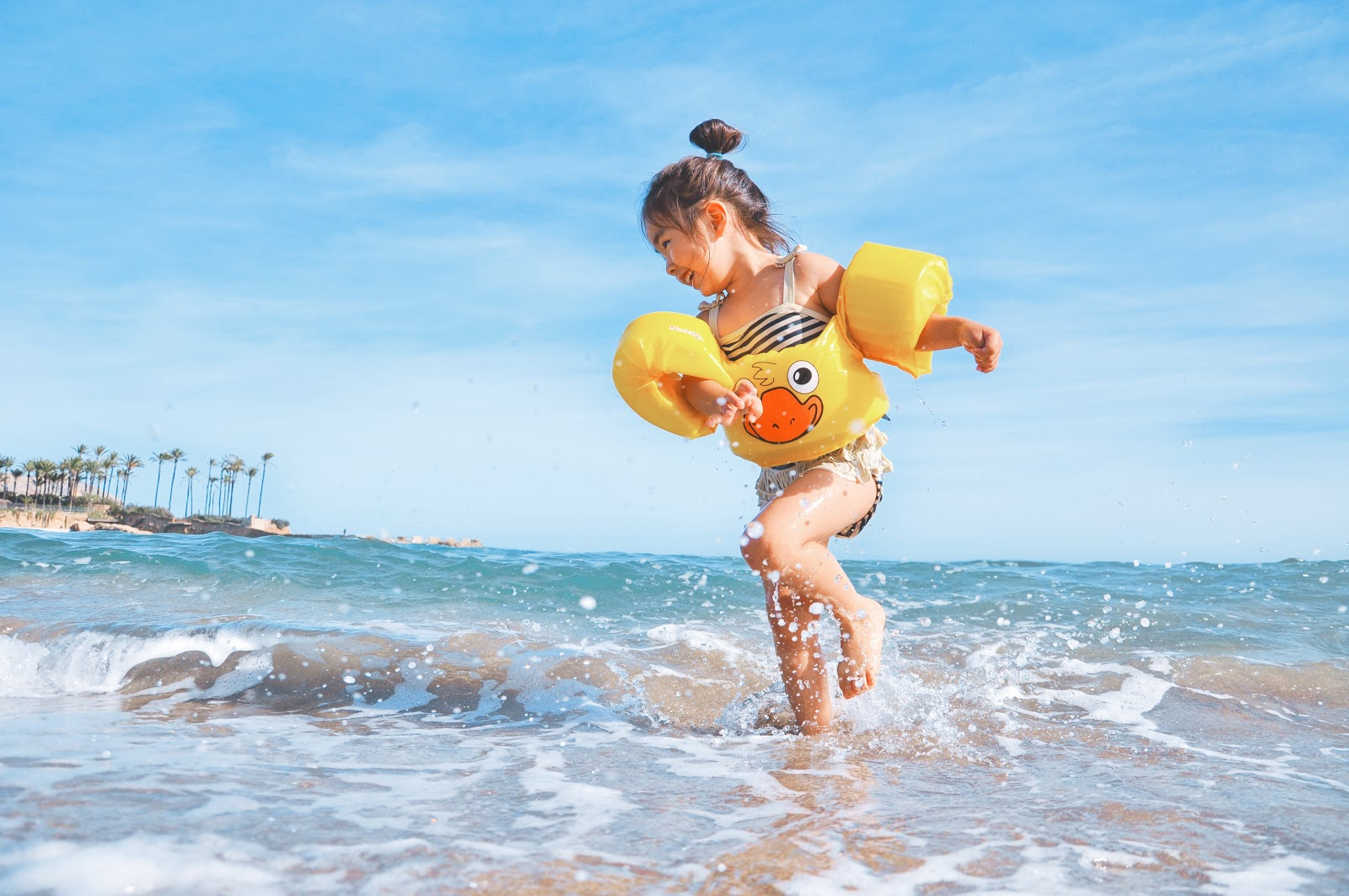 a girl playing with water at the beach