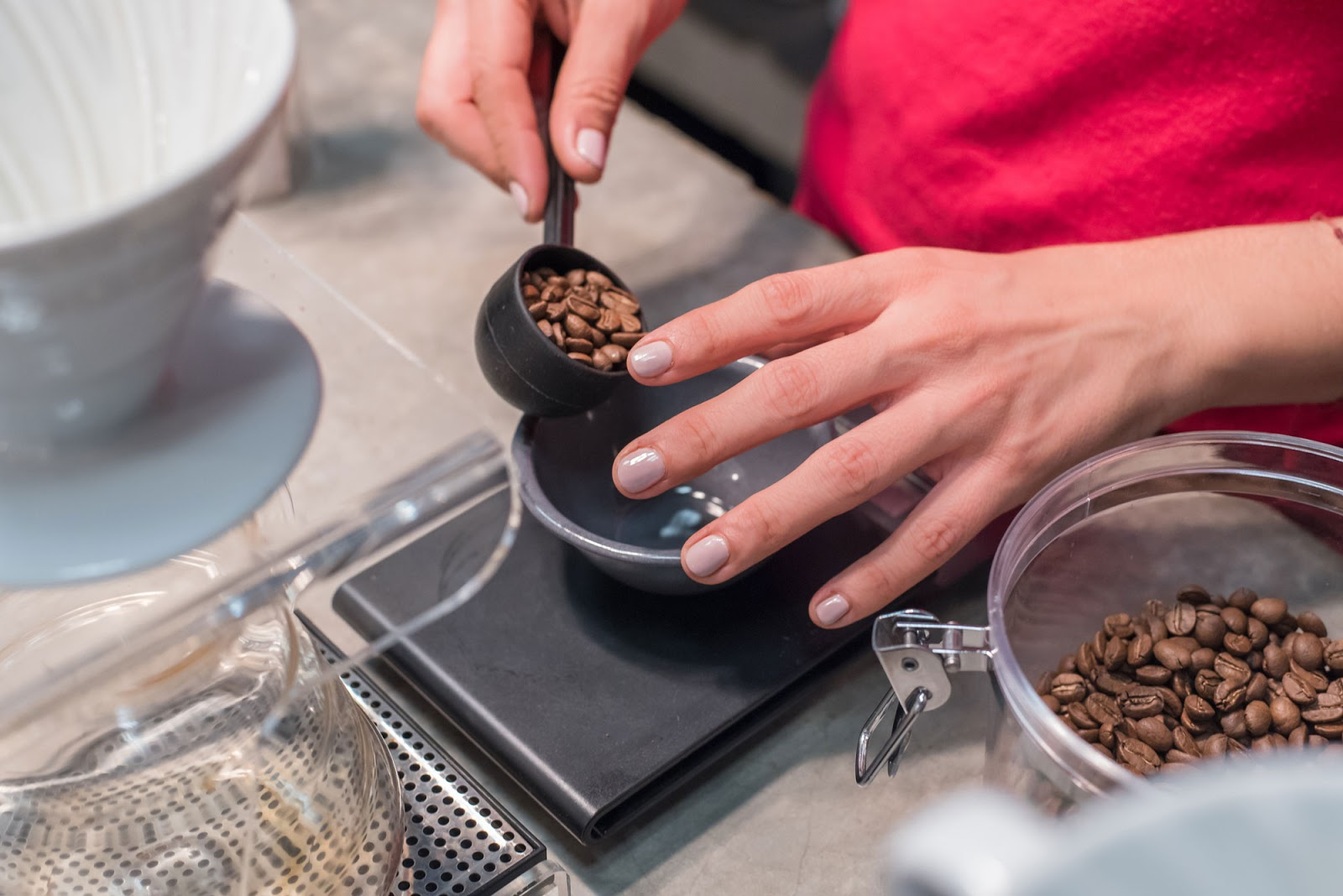 a lady measuring the weight of a scoop of coffee beans