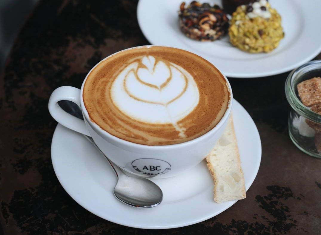 a cup of latte with a biscotti placed on the side
