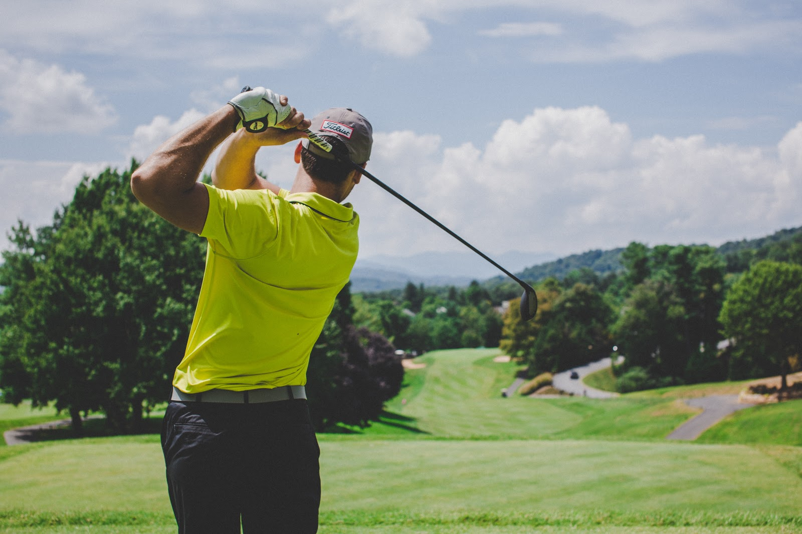 a back shot of a person golfing