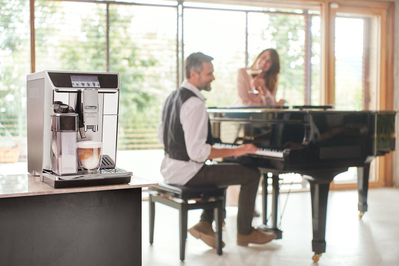 The De'Longhi prima donna elite coffee machine on a table with a man playing the piano in the background