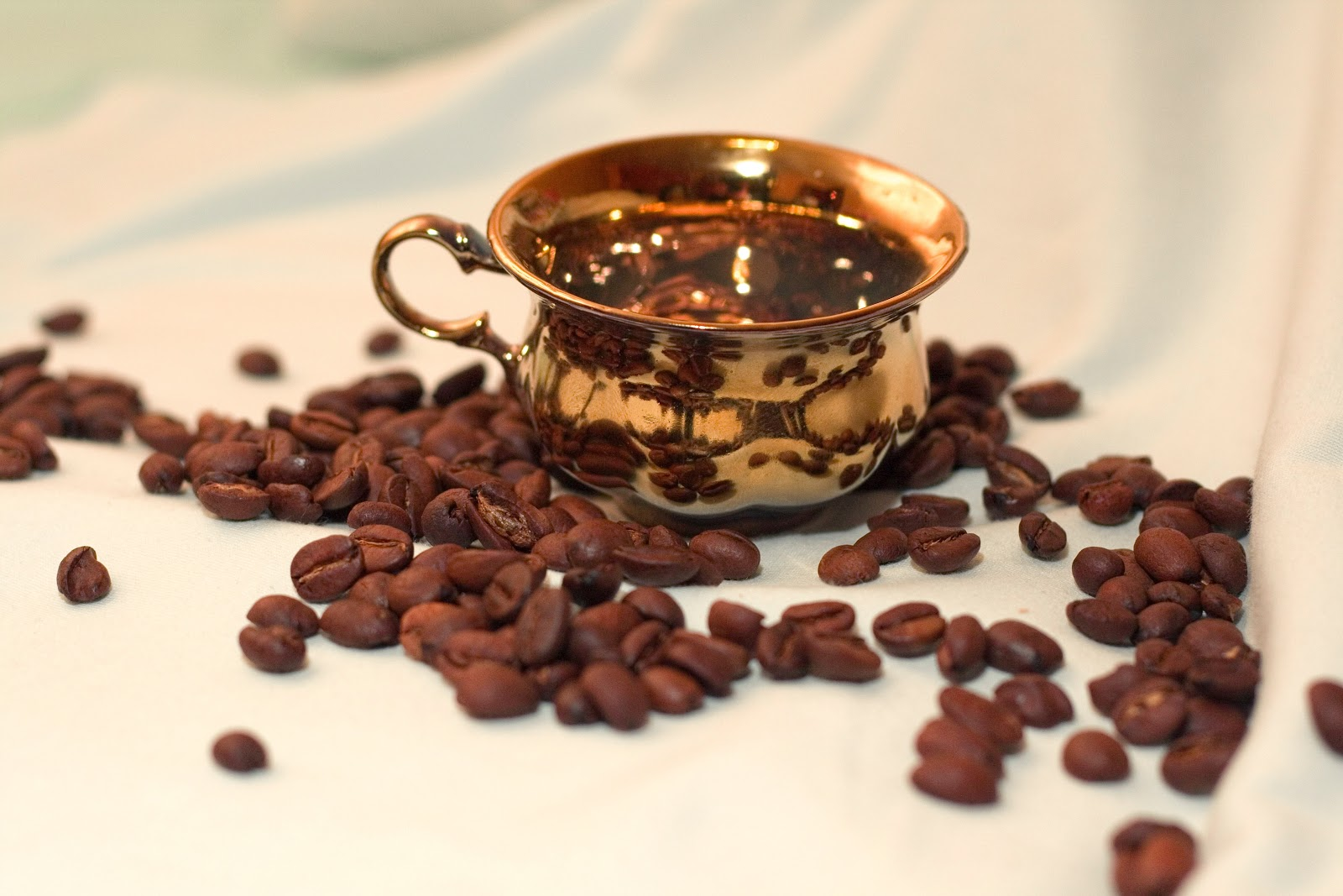 a gold cup surrounded by coffee beans