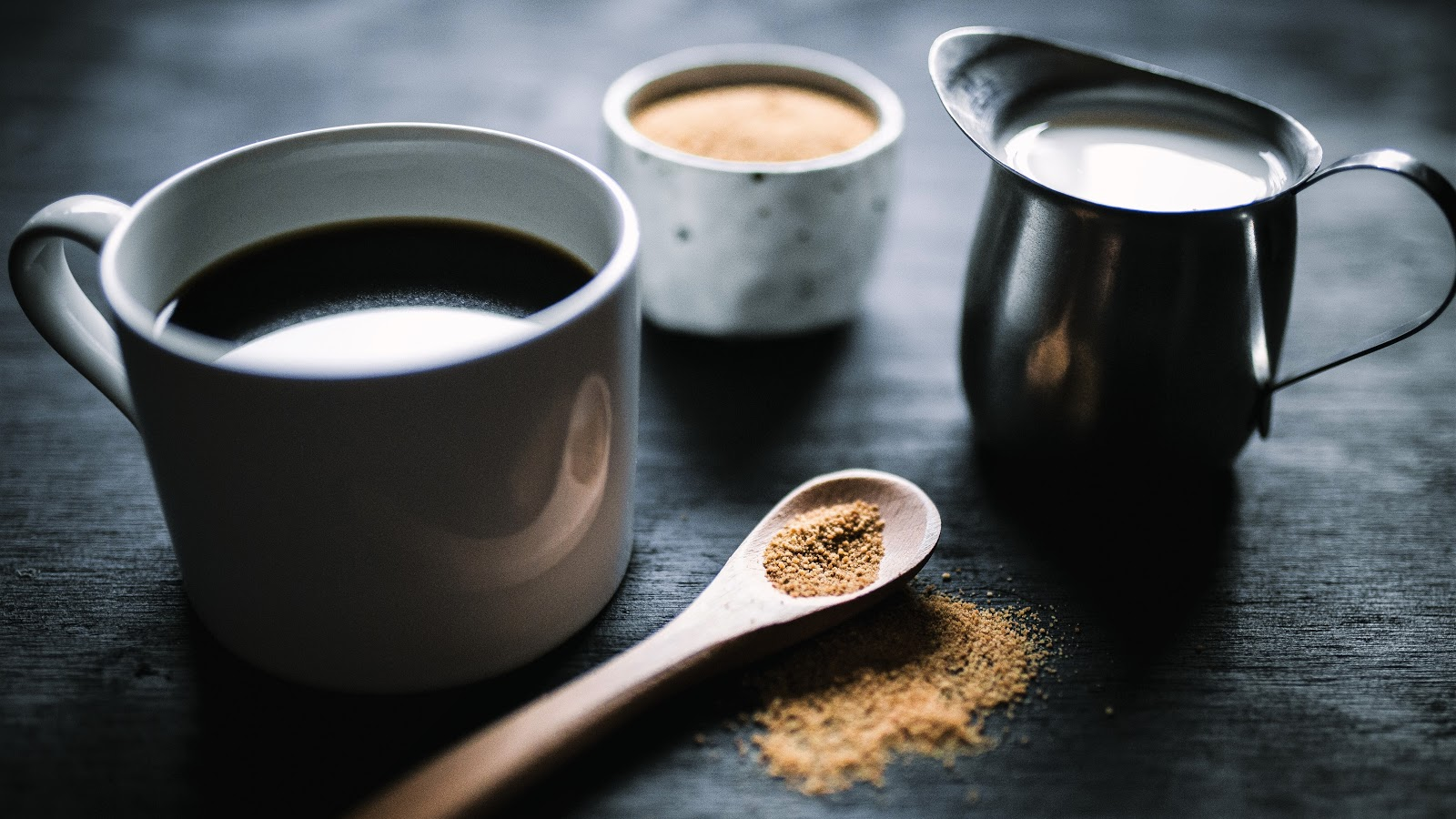 a cup of black coffee, teaspoon of sugar and jar of milk on a table