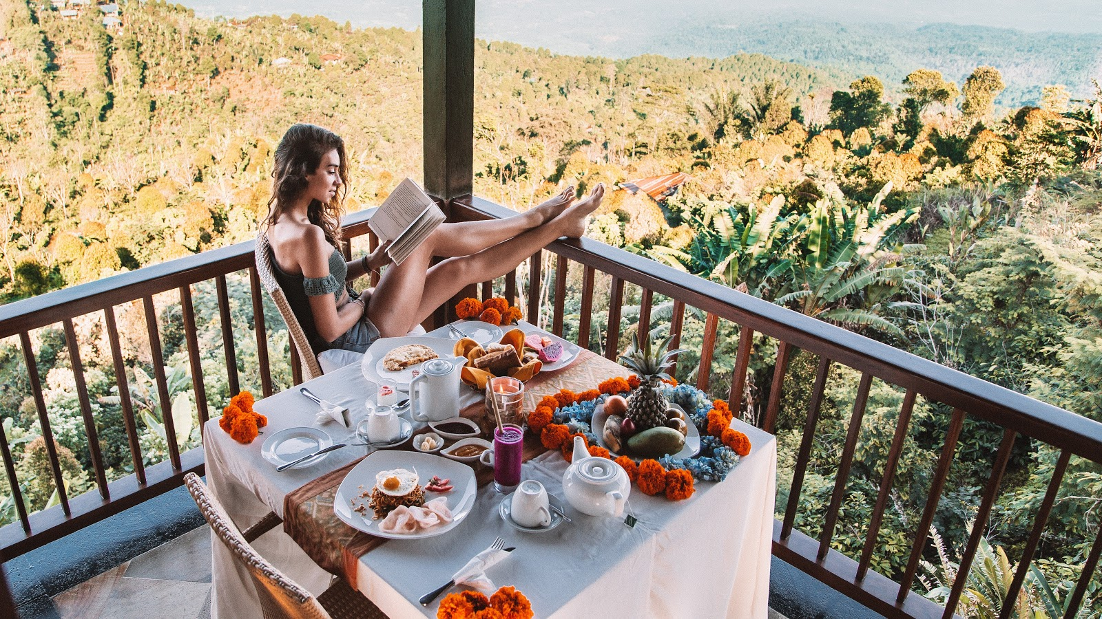 a lady reading a book while having breakfast in the balcony