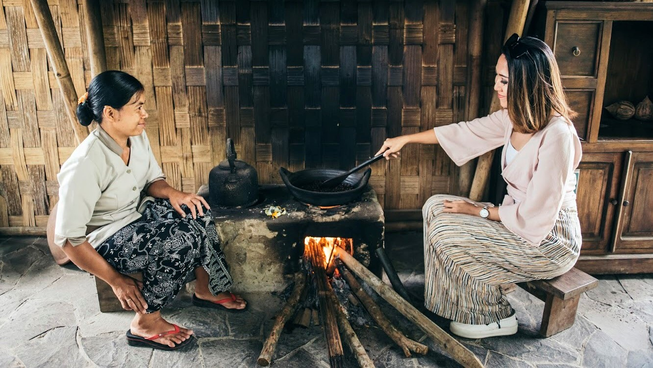 An Asian lady learning how to roast coffee from a coffee roaster