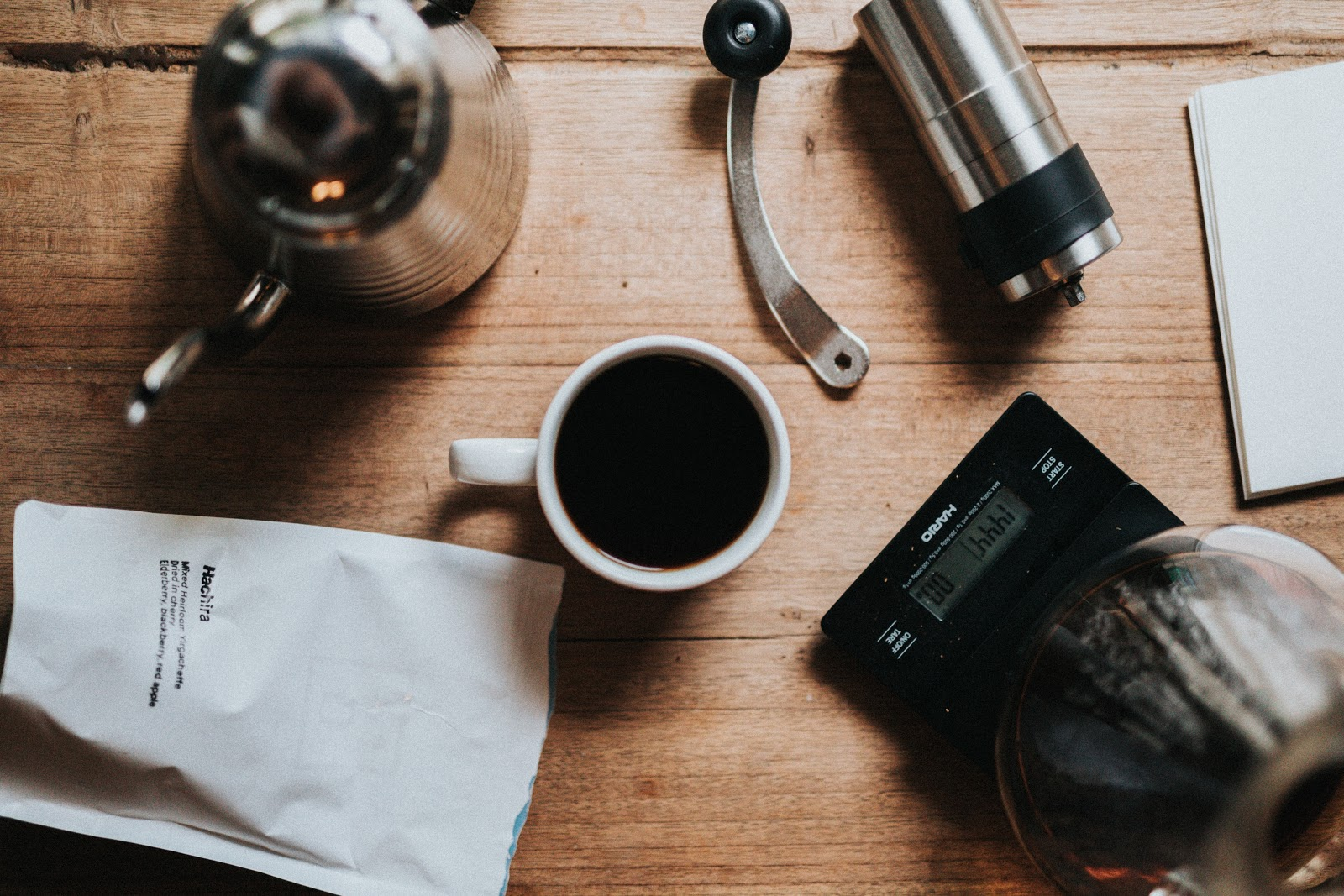 a cup of black coffee with coffee accessories surrounding it