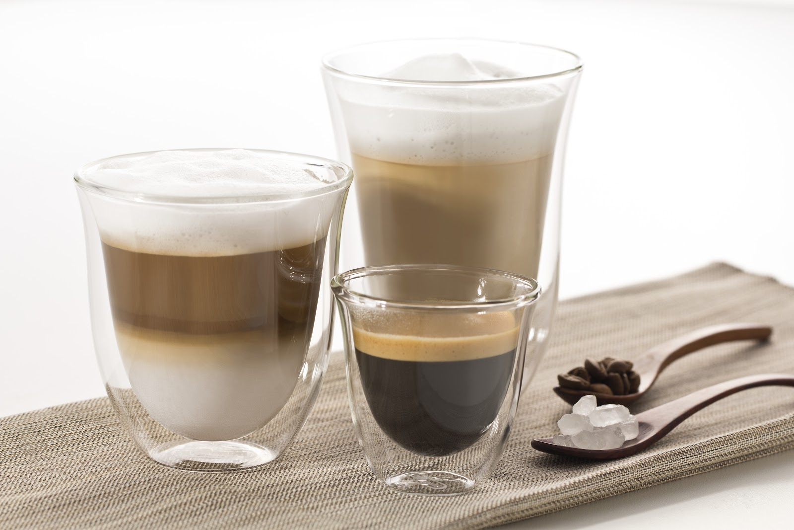 three different types of coffee - an espresso shot, latte, and cuppucino