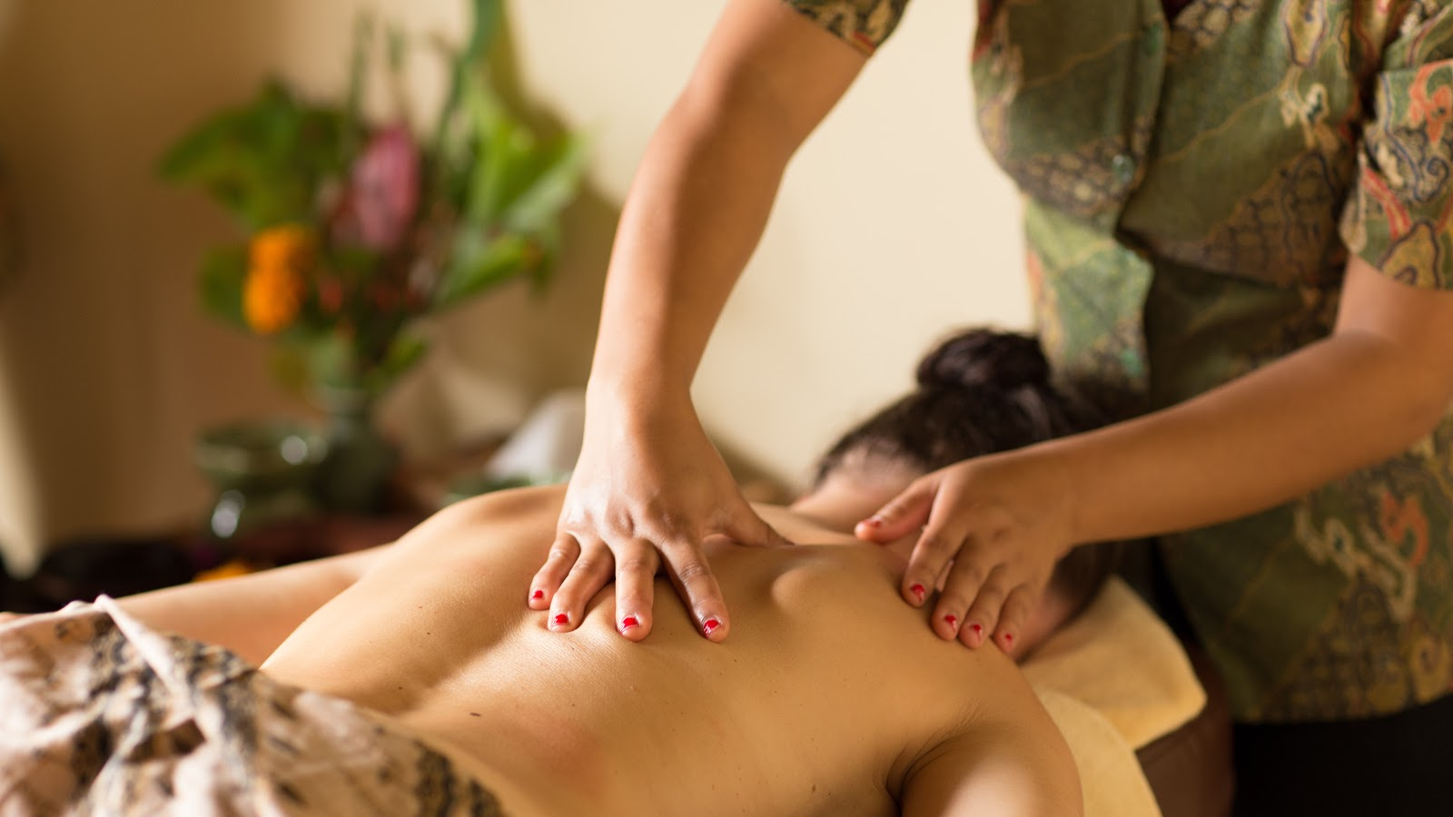 a masseuse massaging the back of an Asian lady