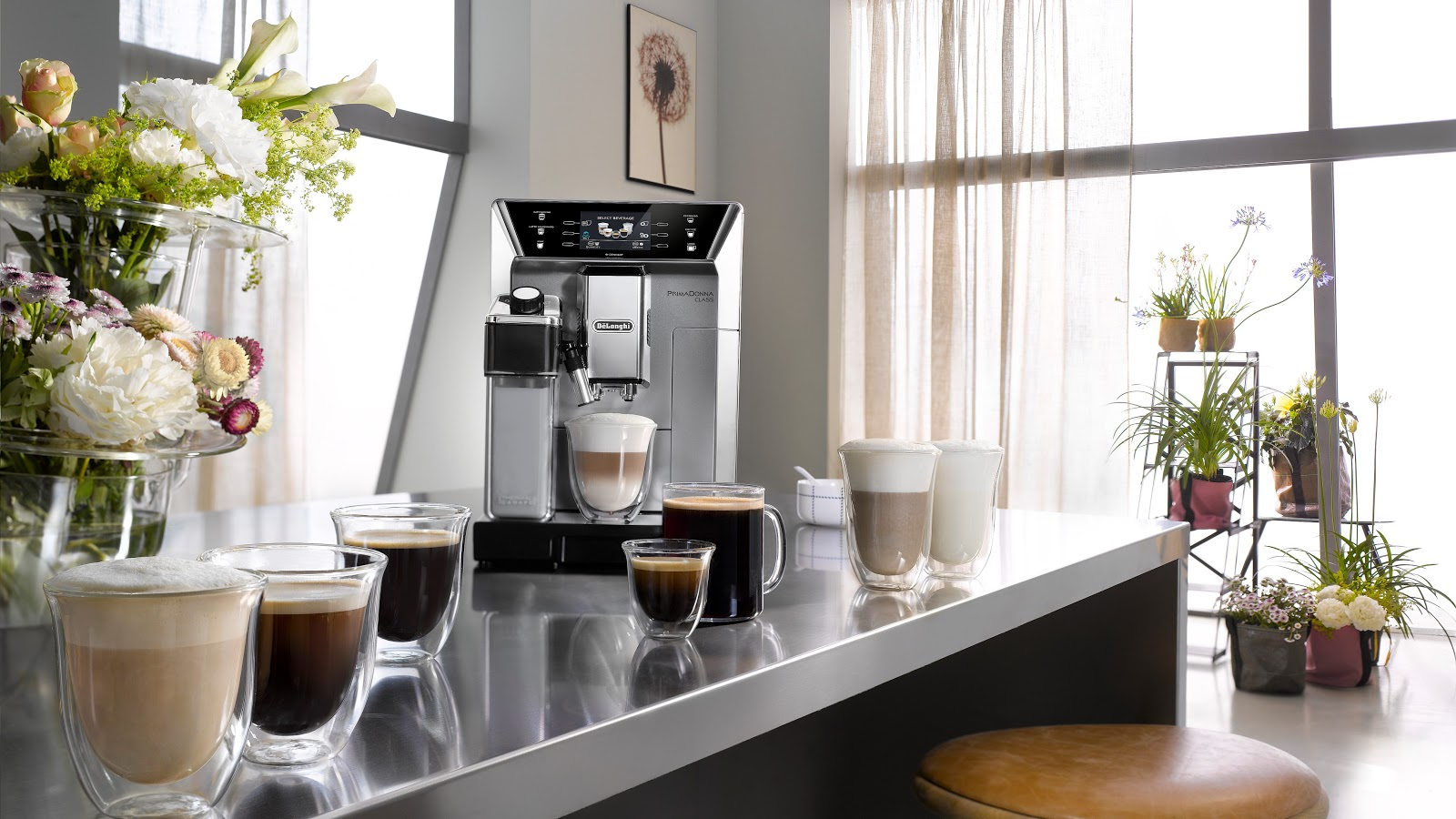 the De'Longhi Prima Donna Elite coffee machine with coffee beverages surrounding it