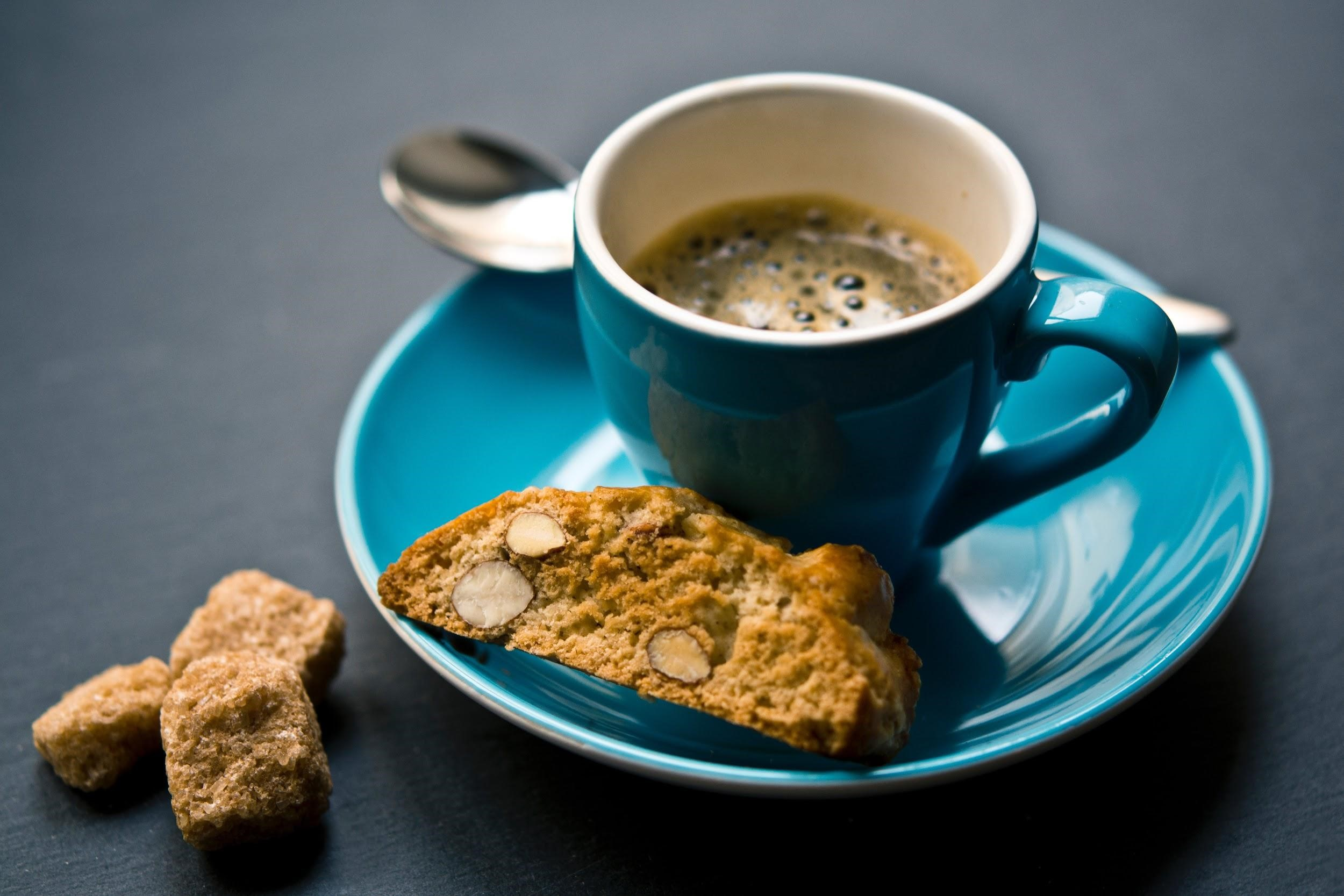 a cup of black coffee served with almond biscotti on the side
