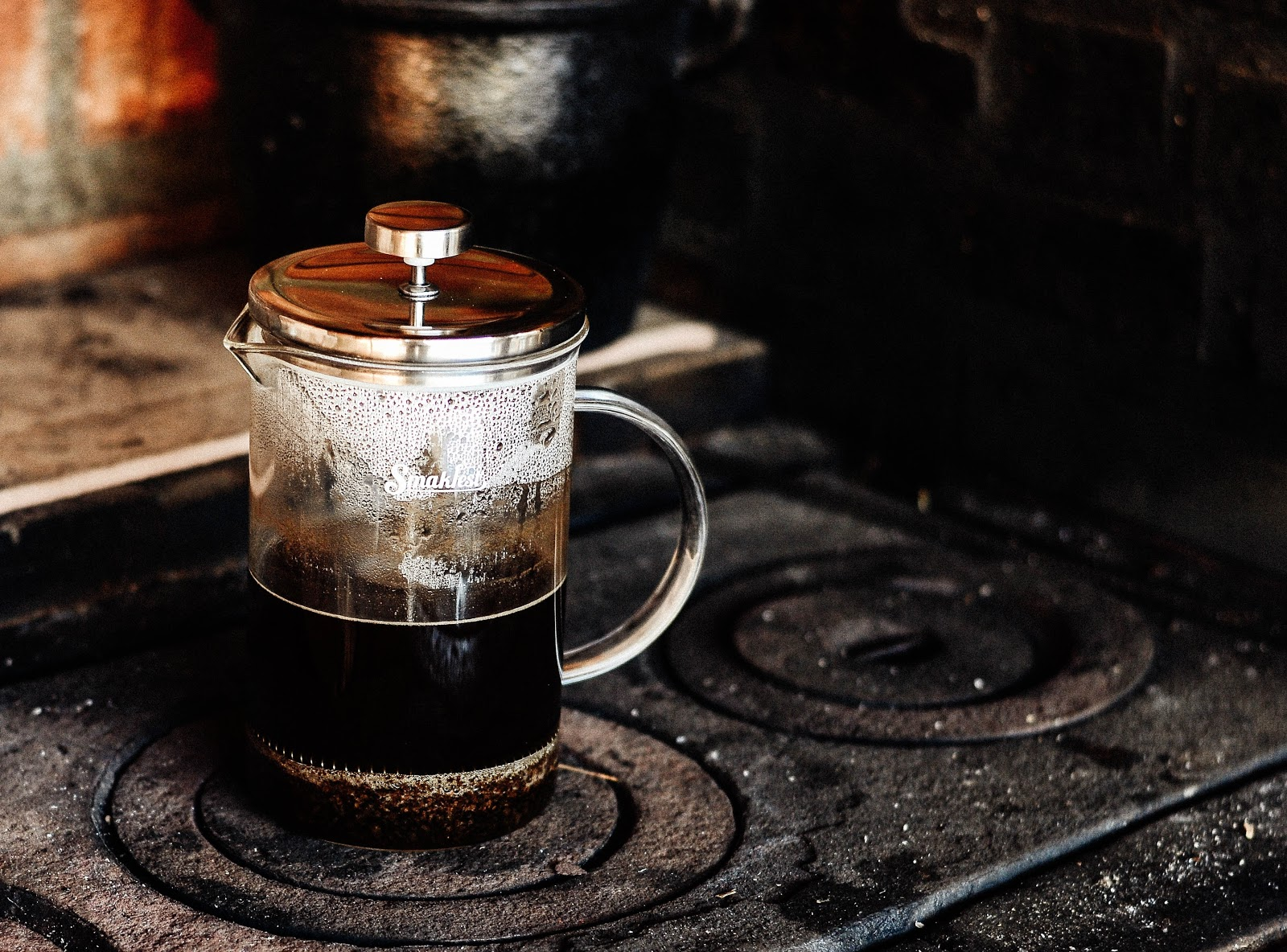 A french press placed on a stovetop