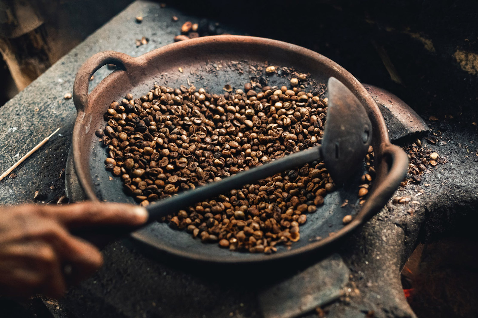 a person roasting coffee beans on a pan