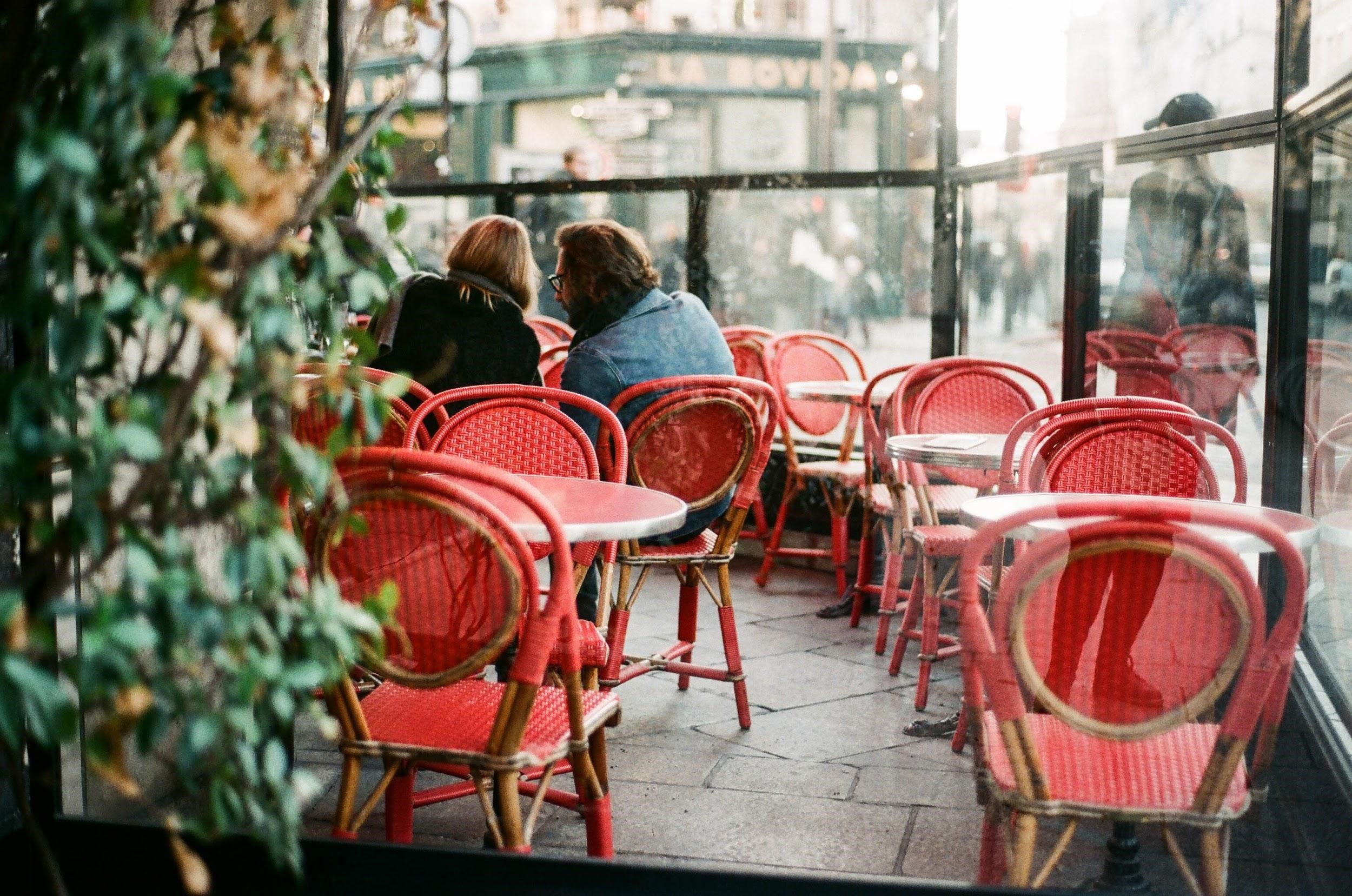 a cafe with outdoor seating and red chairs