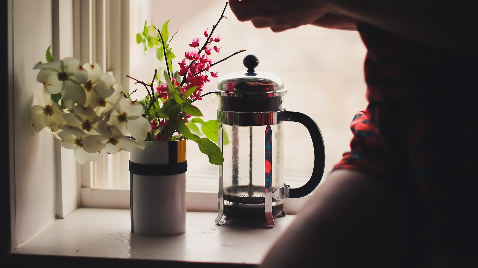 a French Press and vase of flowers placed next to a window