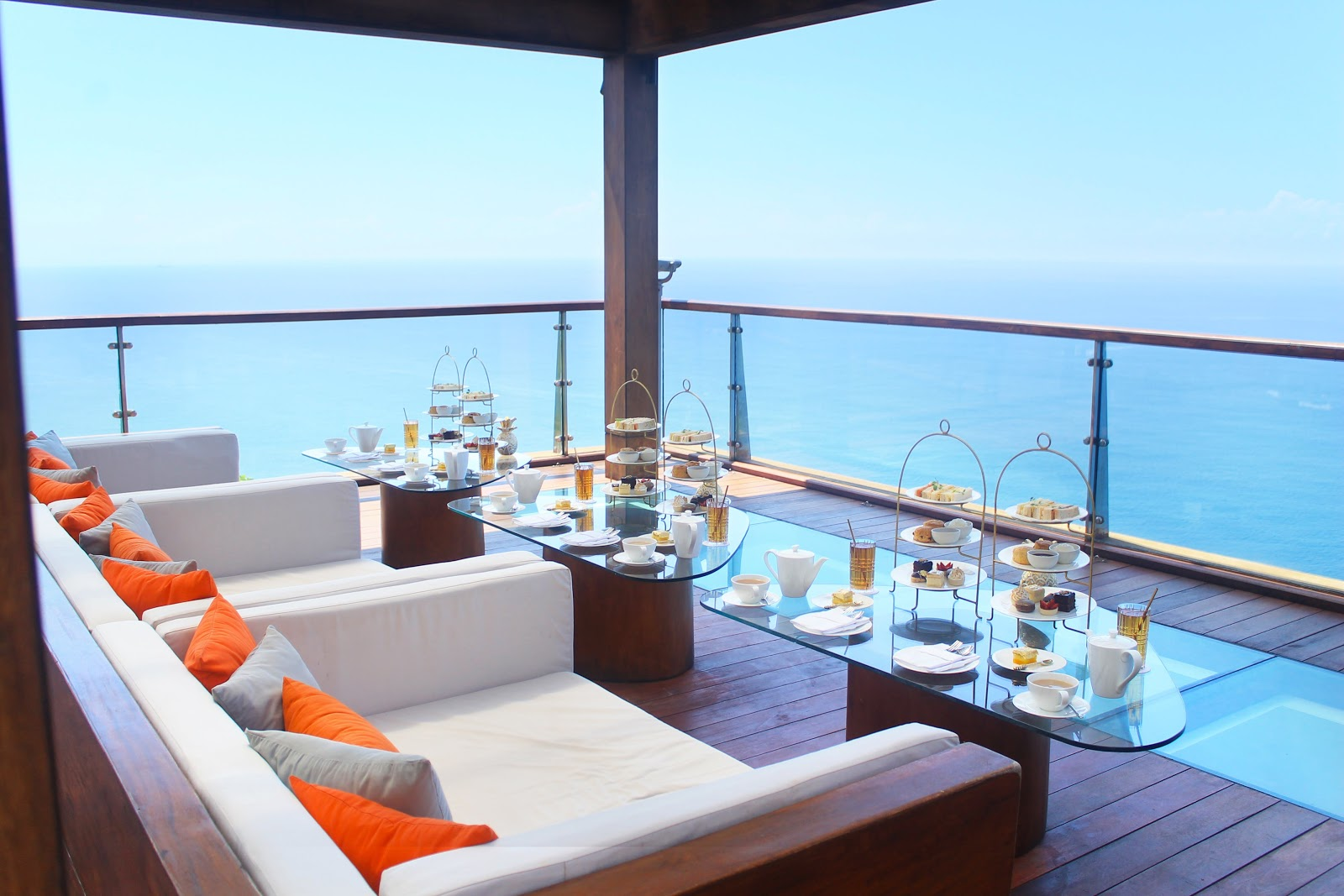 three tables of afternoon tea at a restaurant that overlooks the ocean