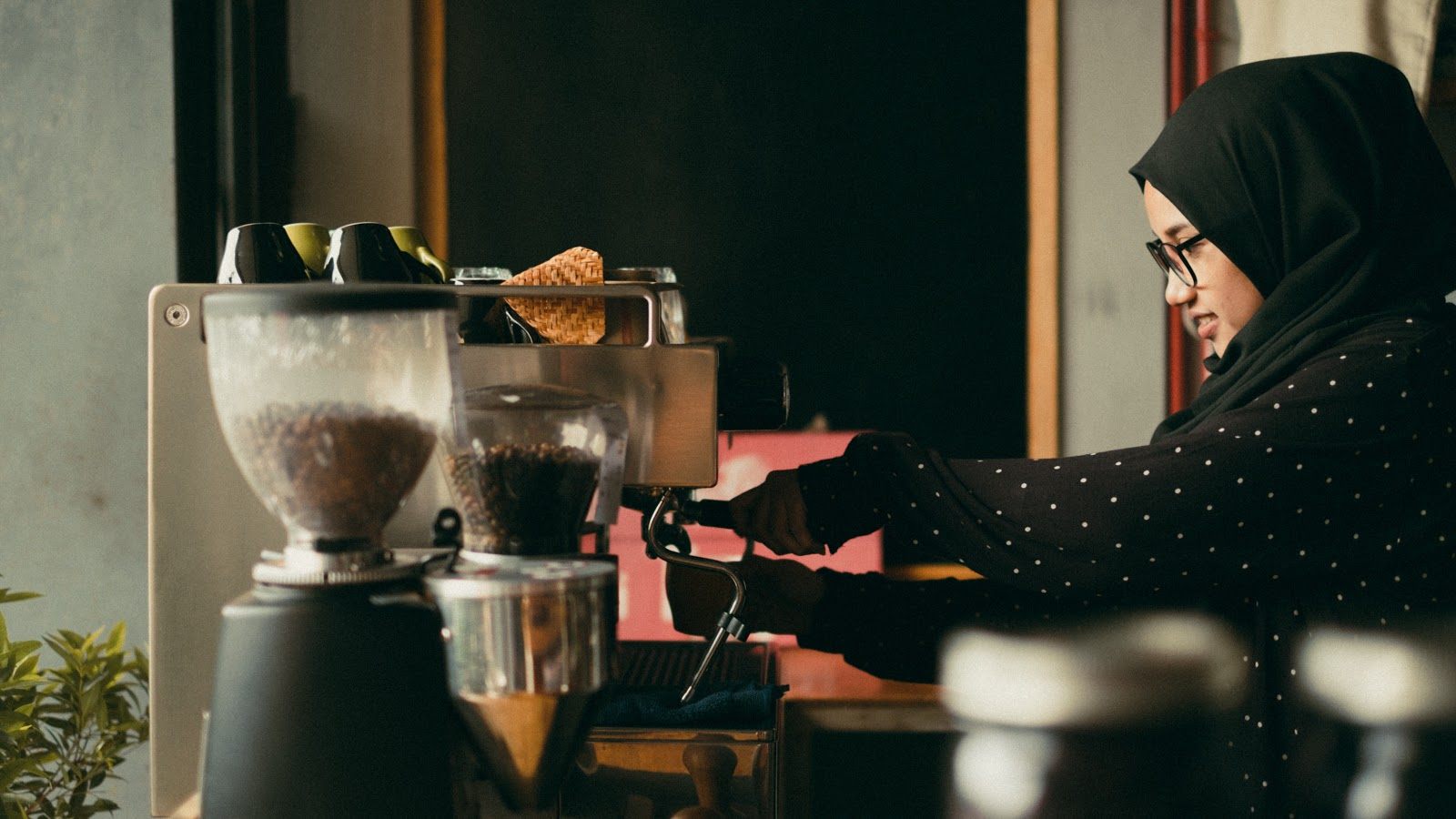 An Asian lady making coffee using an espresso machine at a cafe