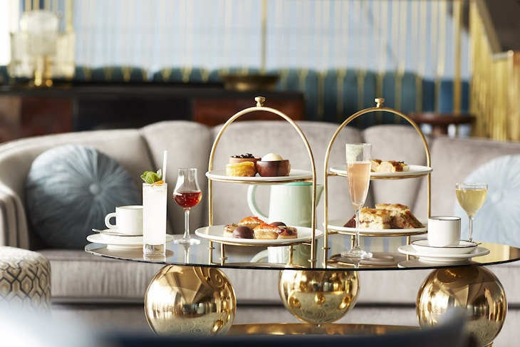 a fancy afternoon tea table with pastries and champagne
