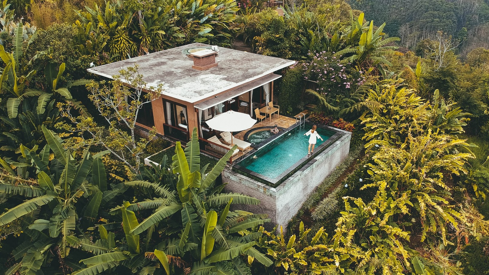 a lady walking along the edge of a swimming pool that is attached to a resort villa