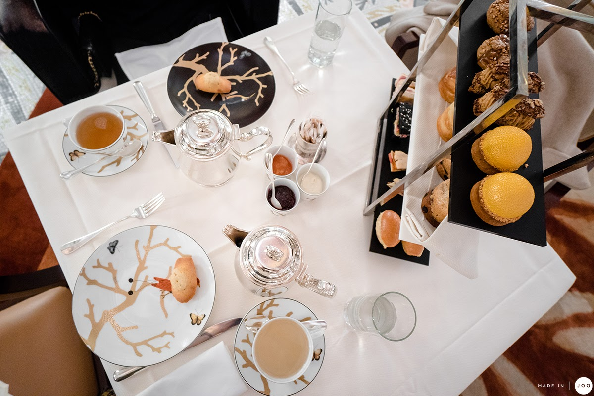 plates and cups of tea with a three-tier cake stand