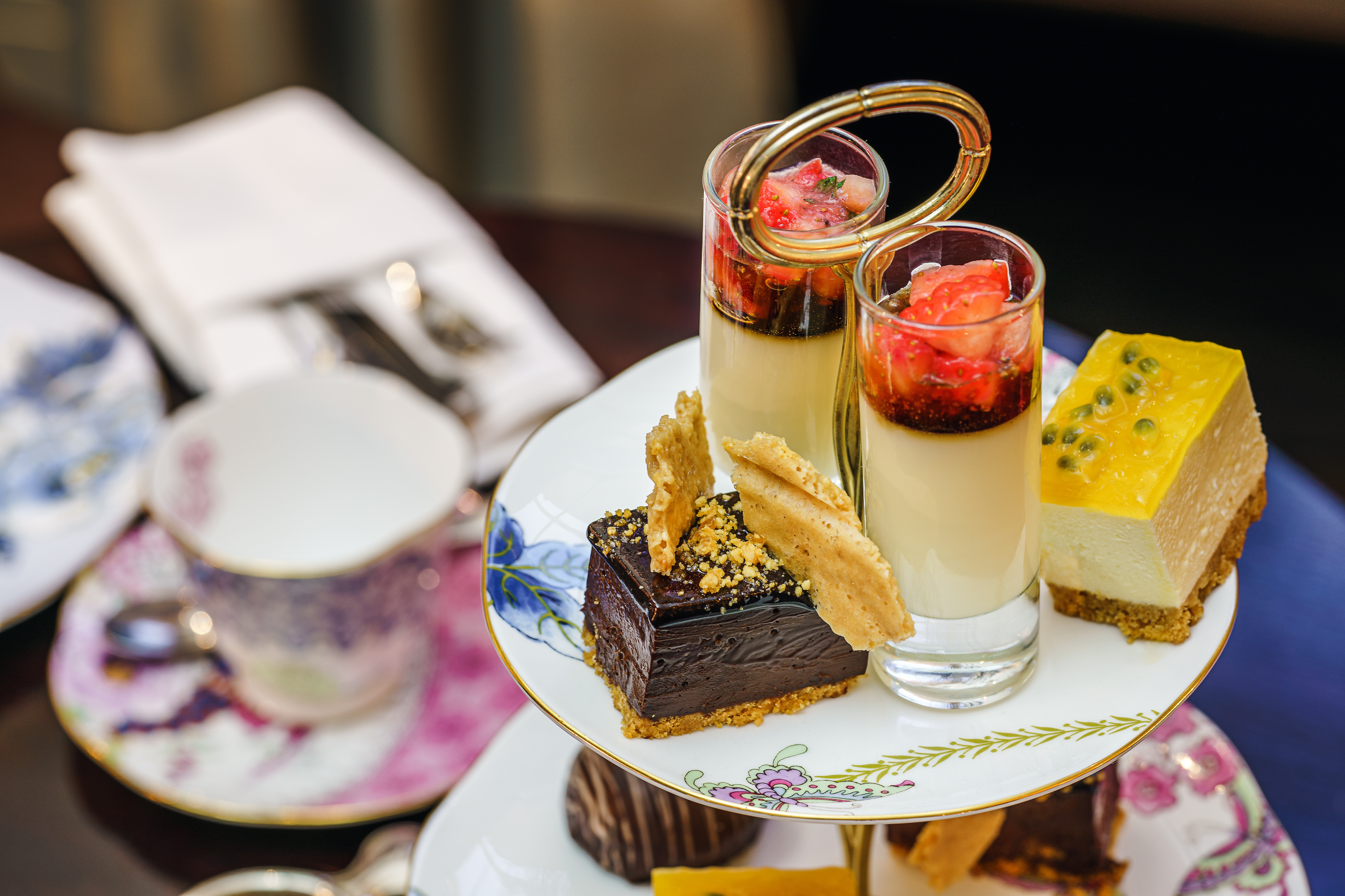 A cup of tea and two-tiered dessert tray