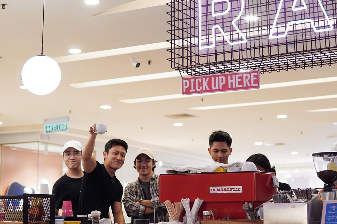 4 men standing behind a coffee counter