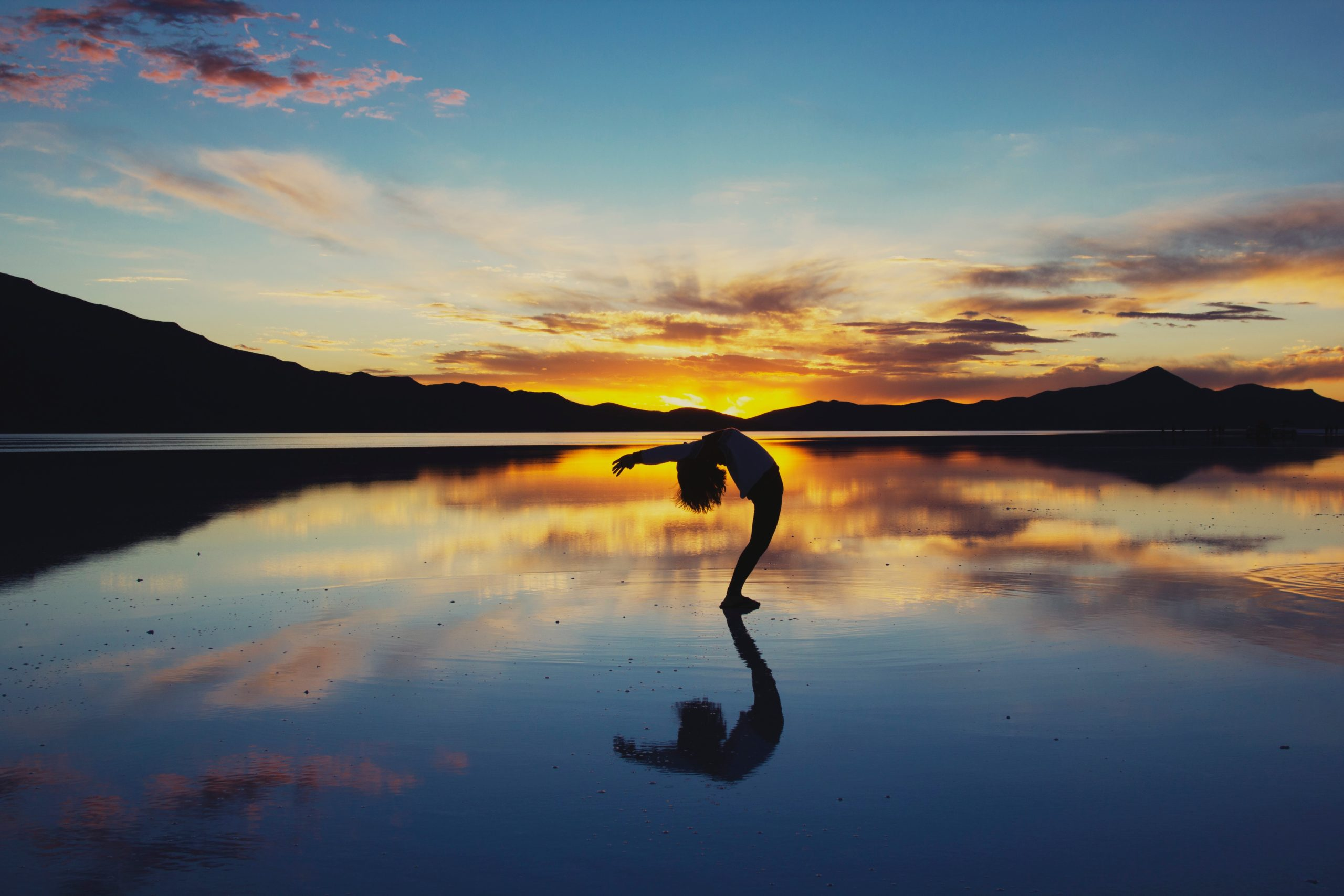 a lady doing yoga while standing on water