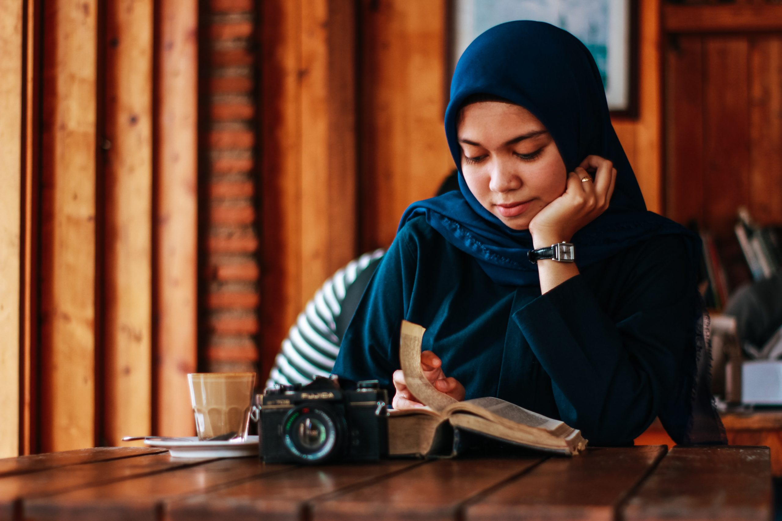 A lady in a hijab reading a book in a cafe