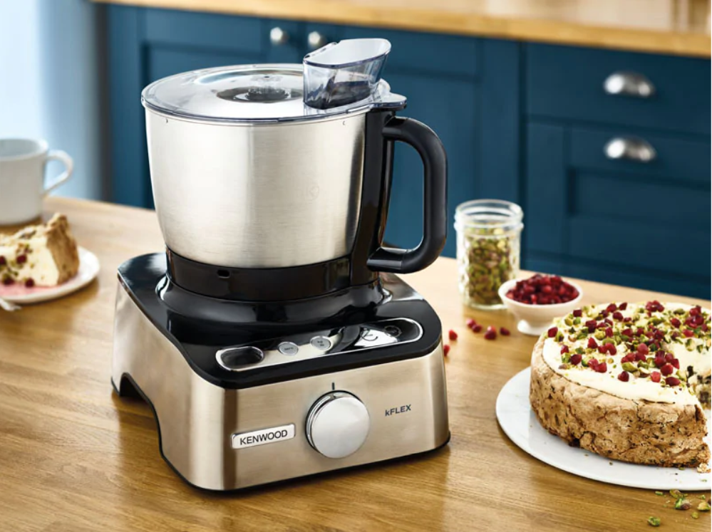 A food processor and a cake on a kitchen tabletop