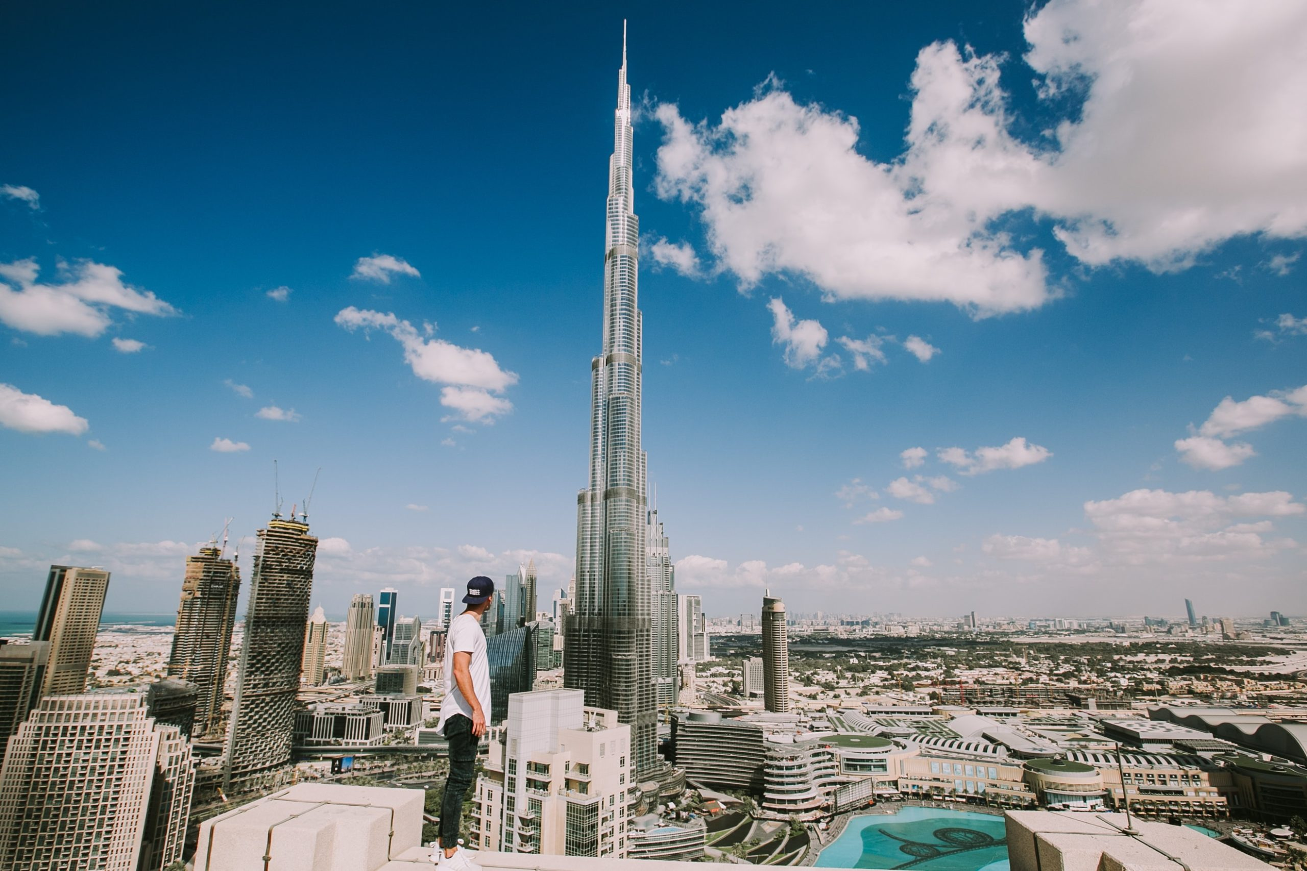 a young man standing atop a roof with the Burj Khalifa in the background