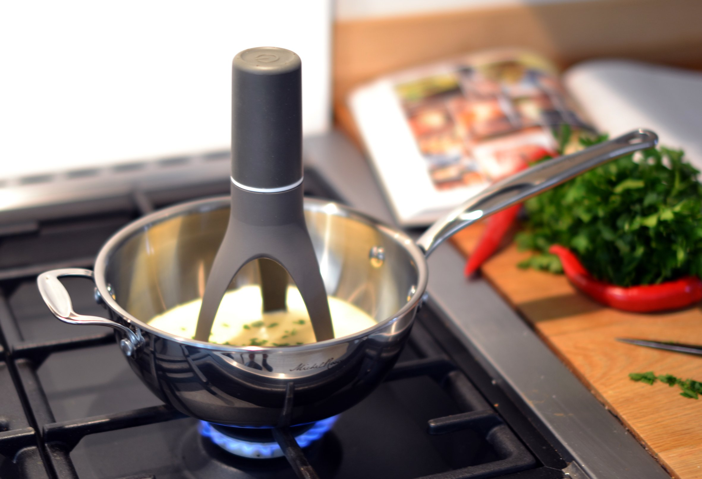 An Automatic Pan Stirrer stirring a creamy soup in a pan