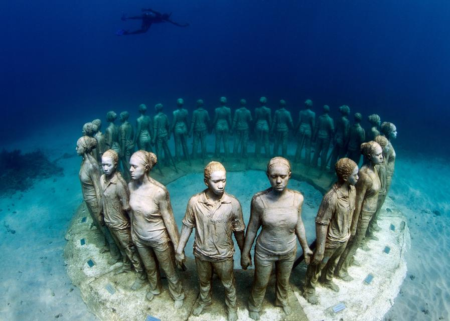human sculptures underwater, standing in a circle