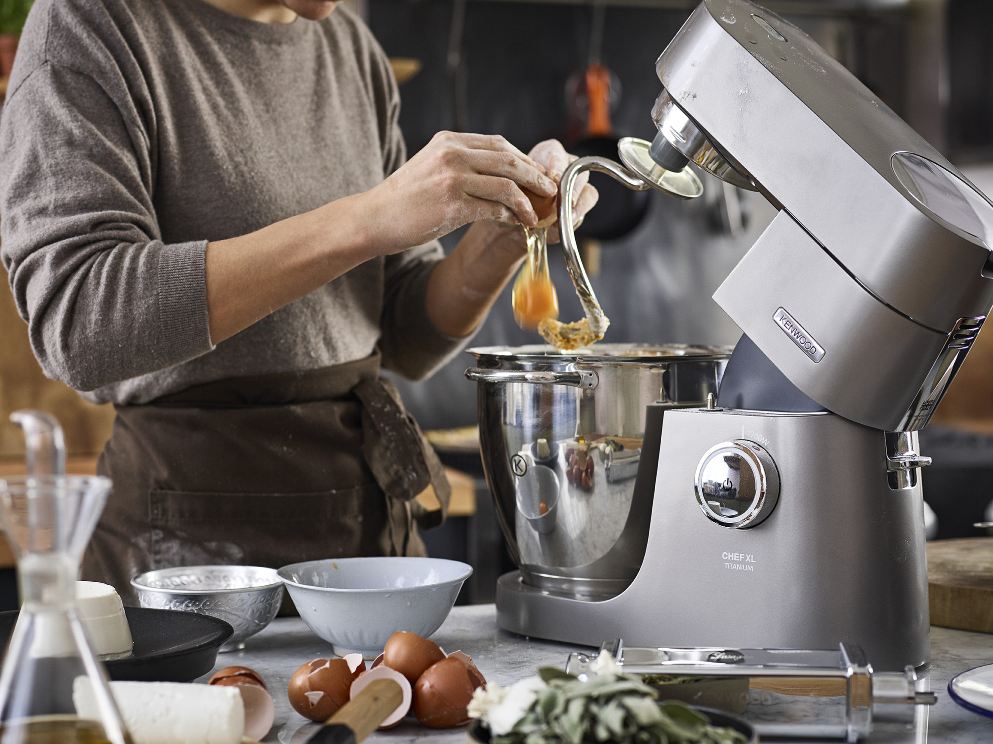 a lady cracking an egg into a standing mixer