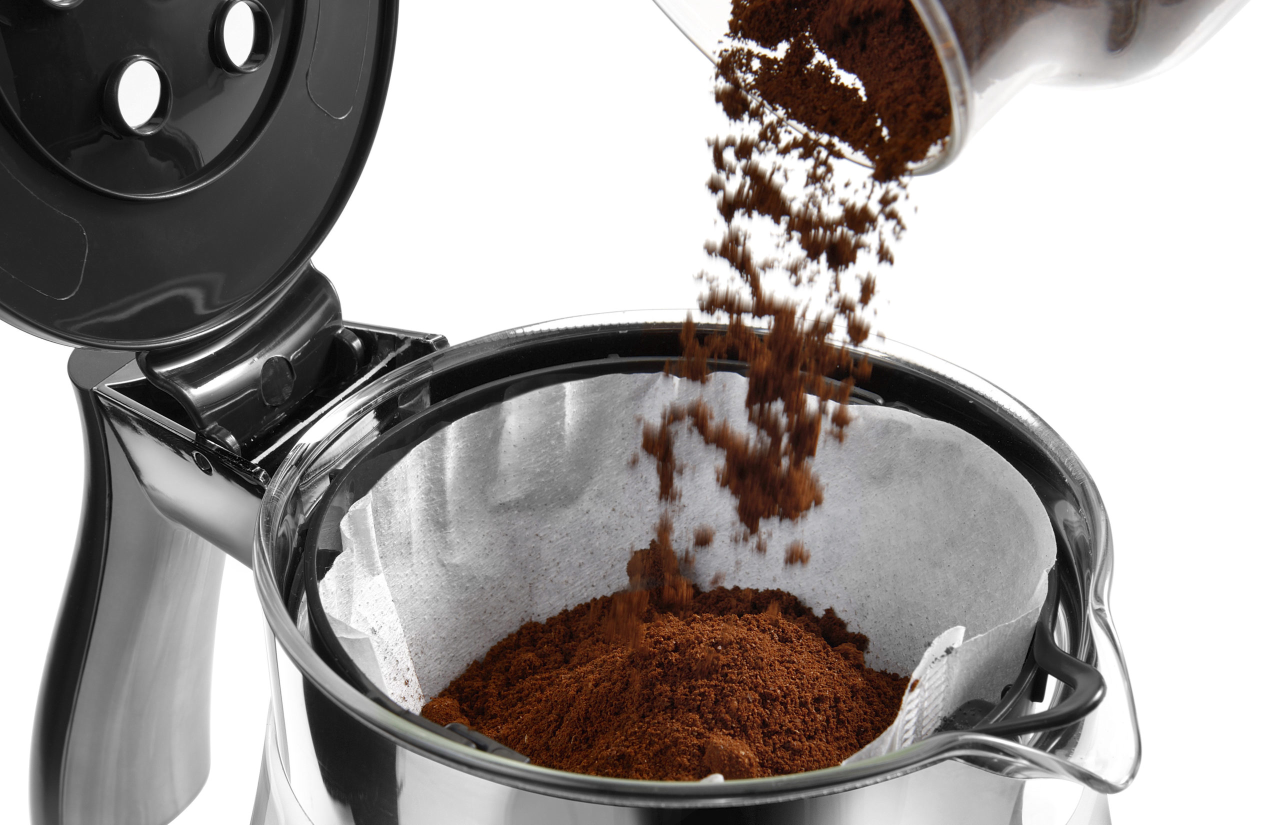 pouring coffee grounds into a drip coffee machine
