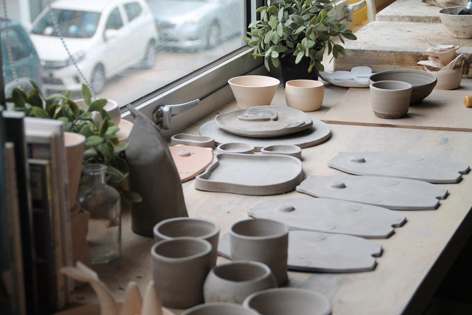 various clay designs drying on a table next to a window
