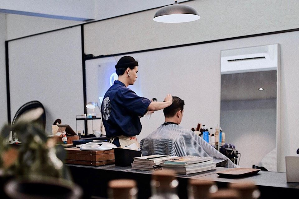a barber cutting a customer's hair