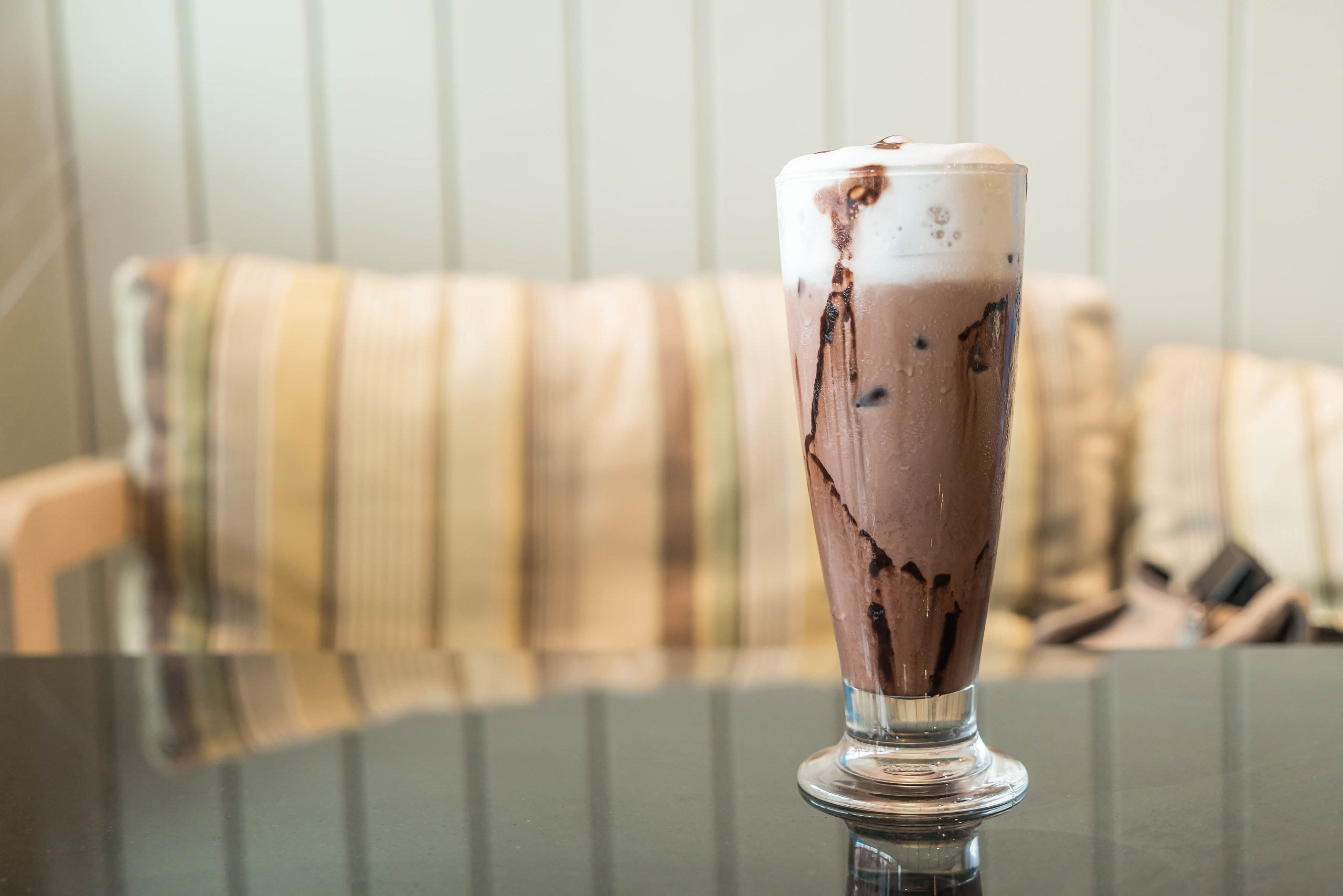 a tall glass of frozen mocha on the table